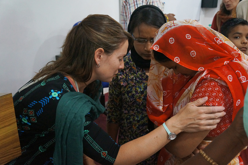 Women praying for each other at the All In Conference in Kanpur
