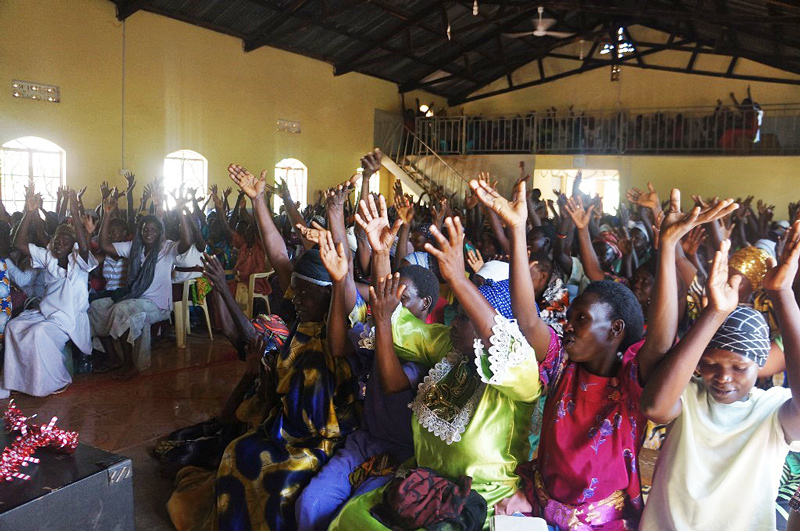 Women worship at the partner mission with All In and One More Child in Uganda.