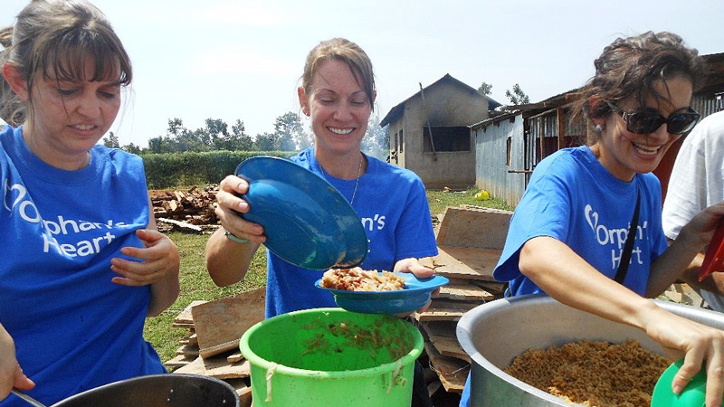 Feeding children in Uganda on the All In and One More Child partner mission trip.