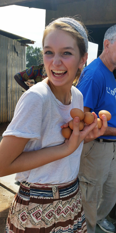 One of the team members for One More Child carries eggs to give children on Egg Day in Uganda.