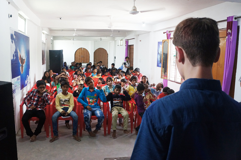 Drew shares his testimony at the All In Conference in India with the children.