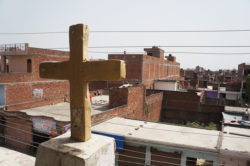 Cross on a rooftop in India