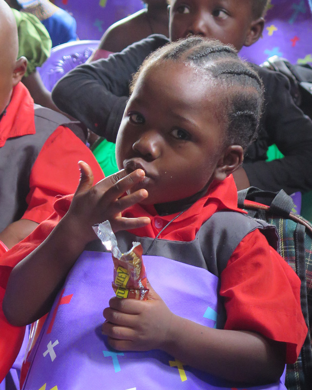 A boy enjoys his snack from the gifts bags delivered to the orphans in Liberia.