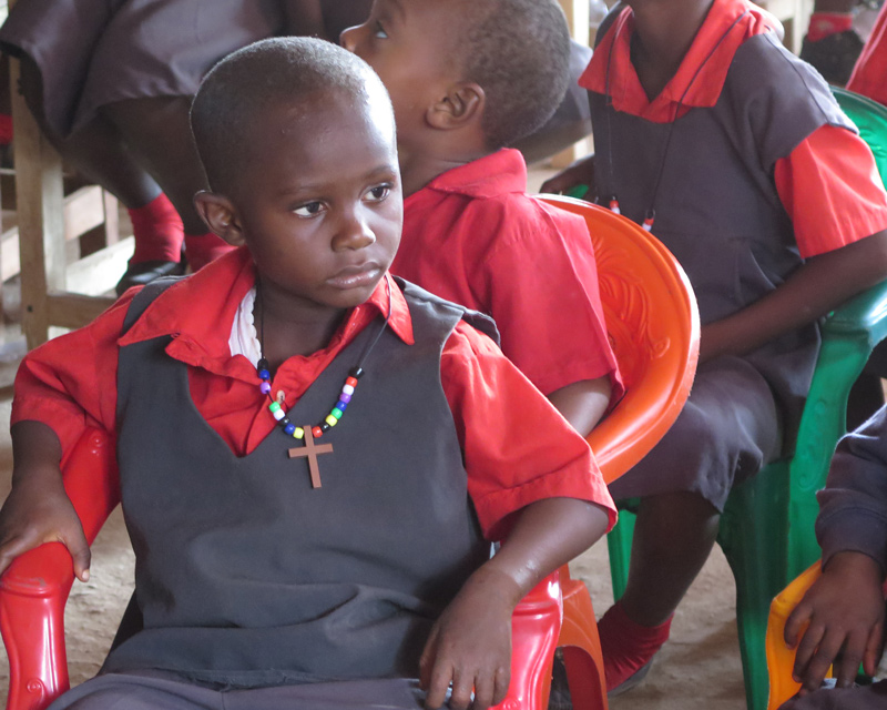 Boy with his cross necklace learning the colors of Easter at the All In Liberia Orphanage visit.