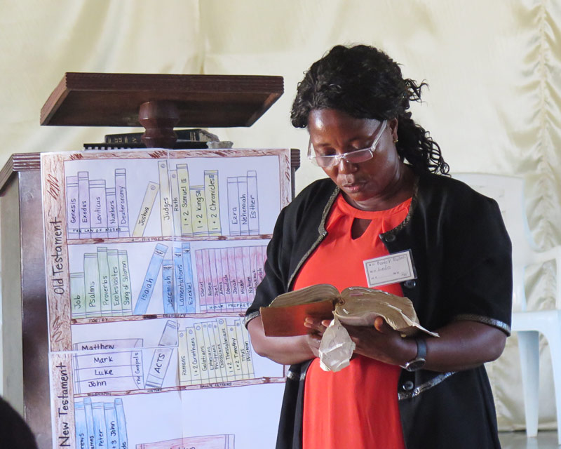 A woman reads from the Bible at the All In Conference in Liberia