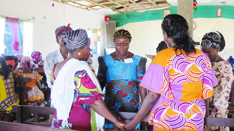 Women praying at the All In Conference in Liberia